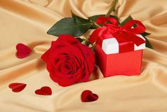 Red roses and gift box on golden fabric Stock Photography
