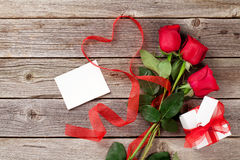Red roses, gift box and heart shape ribbon over wood Stock Photos