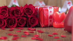 Red roses and gift box on wooden background stock video footage