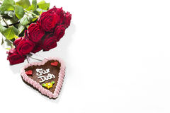 Red roses and gingerbread heart on white background Stock Images