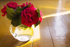 Red roses in a glass vase on wooden table royalty free stock image