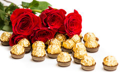 Red roses and gold candy.  Stock Image