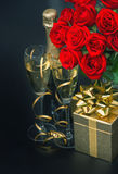 Red roses, golden gift box and and champagne on black background Royalty Free Stock Photos
