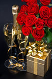 Red roses, golden gift and and champagne Royalty Free Stock Photos