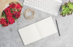 Red roses on grey table with white keyboard, open notebook and boho jewelry. Artist workplace, office concept. Text space Stock Images