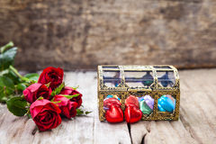 Red roses and heart-shape chocolate for Valentine's Day. Royalty Free Stock Photography