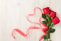 Red roses and heart shape ribbon over wood Stock Image