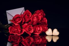 Red roses and heart shaped chocolates on black background royalty free stock photography