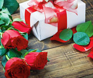 Red roses and holiday gift Stock Image