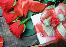 Red roses and holiday gift Royalty Free Stock Image