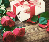 Red roses and holiday gift on a wooden table Royalty Free Stock Images