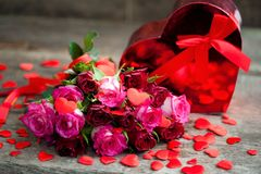 Red roses for the holiday of love and happiness. Mother`s Day, St. Valentine`s Day, birthday, red roses on a wooden table and a gift royalty free stock photo