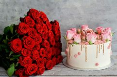 Red roses for the holiday of love and happiness. Mother`s Day, St. Valentine`s Day, birthday, red roses on a wooden table and a gift royalty free stock photos