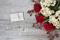 Red roses, hydrangea, hips on wooden background. Place for your text Royalty Free Stock Photo
