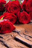 red roses lying on wooden background Stock Image