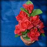 Red roses made of fabric in a vase on a blue cloth. Stock Images