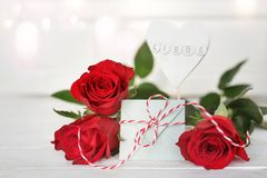 Red roses with a message of love. Still life with red roses and a love message in front of a white background with tender bokeh for valentines day Stock Photo