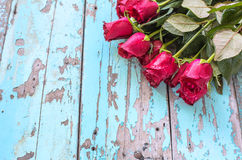 Red roses on old blue wooden background Stock Photos