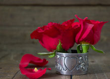 Red roses on old table in antique silver heart serviette holder Stock Photography