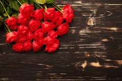 Red roses over dark wooden background Royalty Free Stock Images