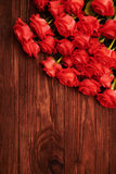 Red roses over wooden brown background Stock Photos