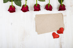 Red roses and paper for congratulations on a wooden background. Royalty Free Stock Photo