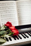 Red roses on piano keys. And music book Stock Photo