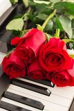 Red roses piano keys romantic background. Stock Images
