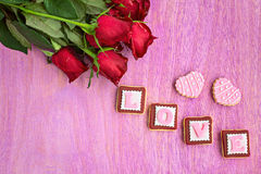 Red roses and pink cookies in shape of LOVE word, on pink wooden stock photo