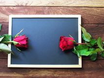 Red and pink roses placed on the blackboard on the wooden background. Valentine`s Day background stock images