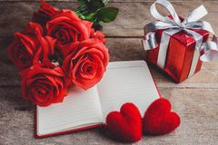 Red roses, red heart, notebook and gift box on a wooden backgrou Royalty Free Stock Image