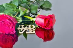 Red roses with reflection in the mirror and the inscription: LOVE. Valentine& x27;s day theme. Romantic moments. stock images