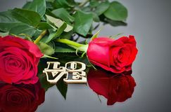 Red roses with reflection in the mirror and the inscription: LOVE. Valentine`s day theme. Romantic moments. stock photo