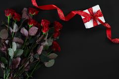 Red roses, ring and gift box on black background. Top view. Flat lay. Copy space. Still life Royalty Free Stock Photography