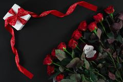 Red roses, ring and gift box on black background. Top view. Flat lay. Copy space. Still life Royalty Free Stock Image