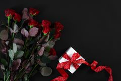 Red roses, ring and gift box on black background. Top view. Flat lay. Copy space. Still life Stock Photo