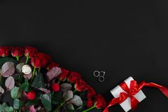 Red roses, ring and gift box on black background. Top view. Flat lay. Copy space. Still life Royalty Free Stock Images