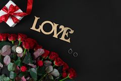 Red roses, ring and gift box on black background. Top view. Flat lay. Copy space. Still life Stock Image