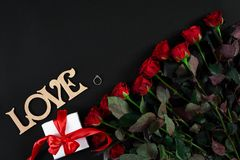 Red roses, ring and gift box on black background. Top view. Flat lay. Copy space. Still life Royalty Free Stock Photo