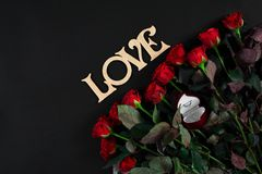 Red roses, ring and gift box on black background. Top view. Flat lay. Copy space. Still life Royalty Free Stock Photos