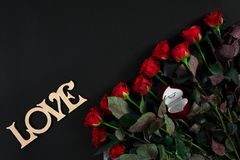 Red roses, ring and gift box on black background. Top view. Flat lay. Copy space. Still life Stock Images