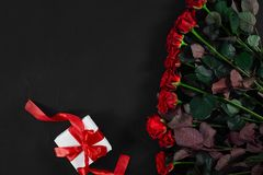 Red roses, ring and gift box on black background. Top view. Flat lay. Copy space. Still life Stock Photos