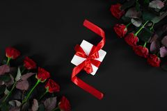 Red roses, ring and gift box on black background. Top view. Flat lay. Copy space. Still life Valentine`s Day Royalty Free Stock Photos