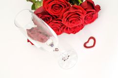 Red roses and a ring in a glass Royalty Free Stock Images