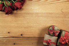 Red roses and three gift boxes on wood with copy space. Red roses and three gift boxes on light wood with copy space Stock Photos