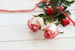 Red roses tied with a ribbon and hearts Royalty Free Stock Photography