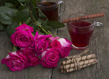 Red roses and two glasses of tea Stock Photo