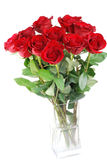 Red roses in a vase. Red roses in a glass vase isolated stock photo