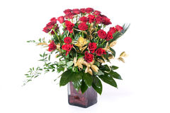 Red roses in vase. Red roses with green and gold leafs in a glass vase stock image