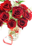 Red Roses In Vase With Heart. A bouquet of deep red roses in a vase with red heart shape, shallow depth of field with selective focus stock photos